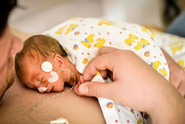 Ist das Baby stabil genug, dann kommt es auf die Brust von Mama oder Papa und wird zusätzlich mit einer angewärmten Decke geschützt. Dort kann es den Herzschlag, die Nähe und den Geruch der Eltern spüren und aufnehmen. (#02)